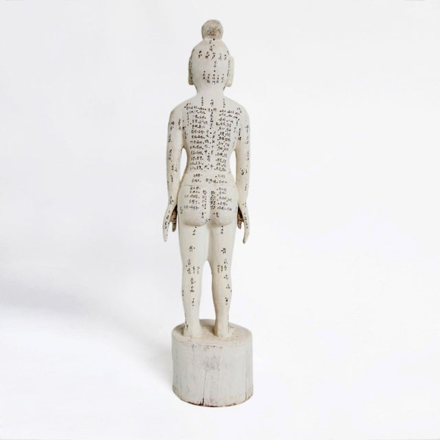 Chinese wood carved acupuncture teaching statue in Medium size. Ink inscriptions cover the body showing notations of...