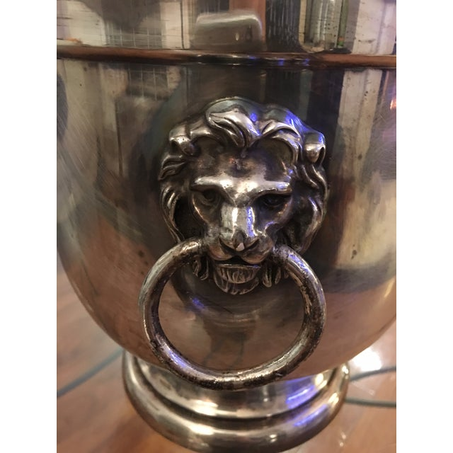 Silver ice bucket depicting lion heads for handles and a white glass container. SYMBOLISM OF THE LION HEAD An ancient...