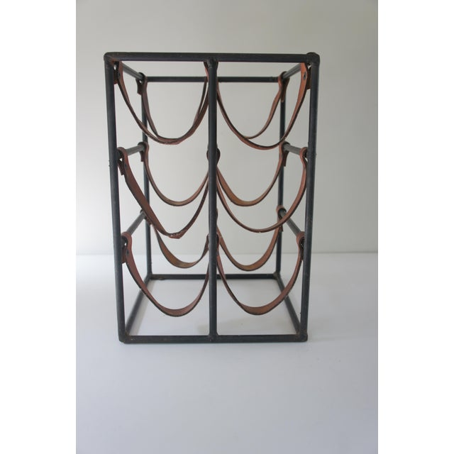 Mid-century modern wrought iron and leather sculptural wine rack designed by Arthur Umanoff. Beautiful, sculptural design,...