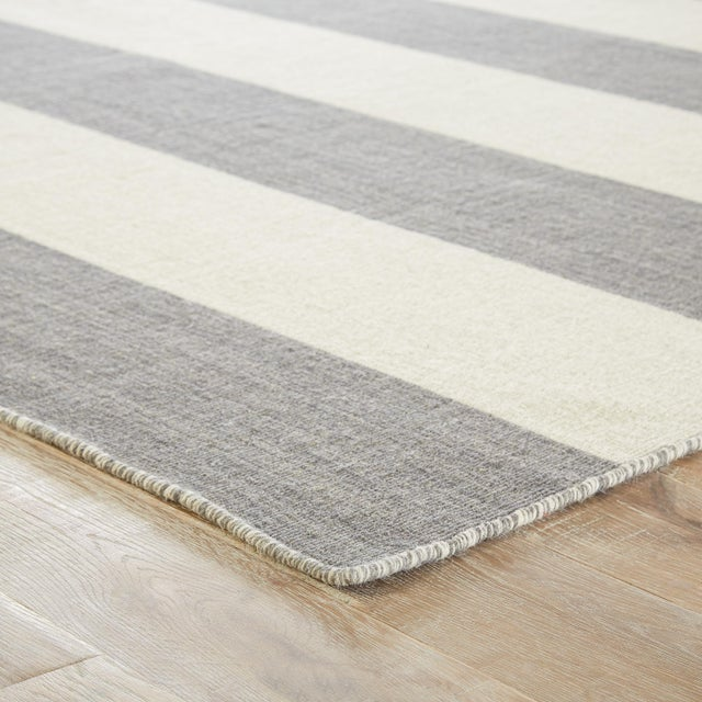 This classic dhurrie-style area rug features gray and white bold stripes, perfect for a transitional space. Constructed of...