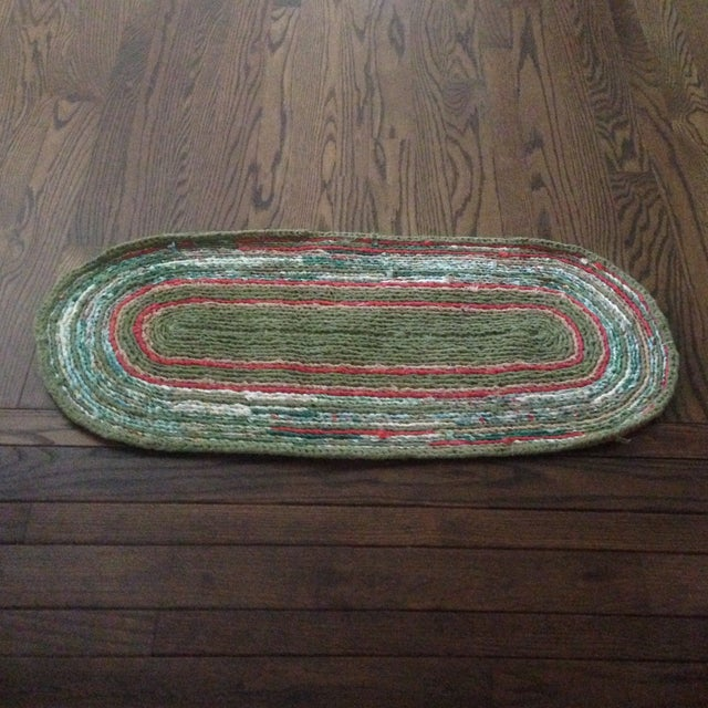 A vintage handmade oval shaped rag rug. Beautiful, vibrant tones of green, aqua, coral and cream. Great accent for a...