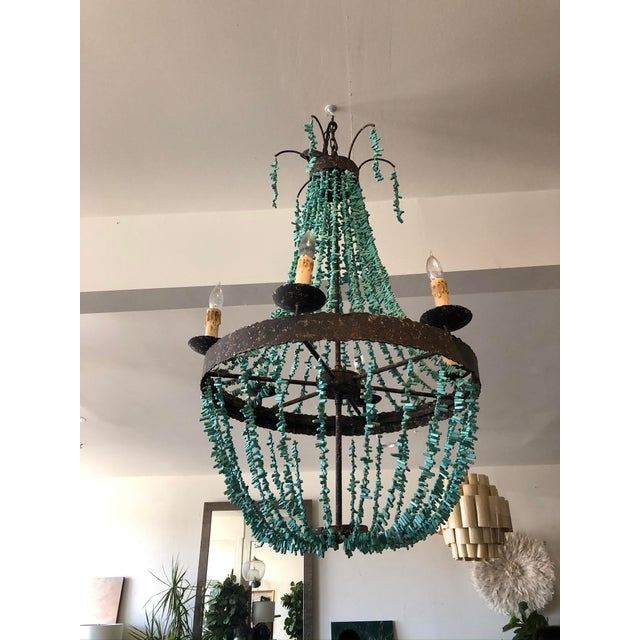 A fun and bright twist on the empire chandelier, this romantic light fixture is made with draping strands of faux...