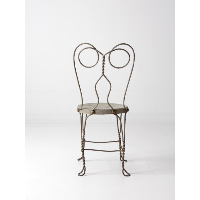 A vintage ice cream parlor chair. The gainsboro (light gray) metal chair features twisting and curving designs and a metal...
