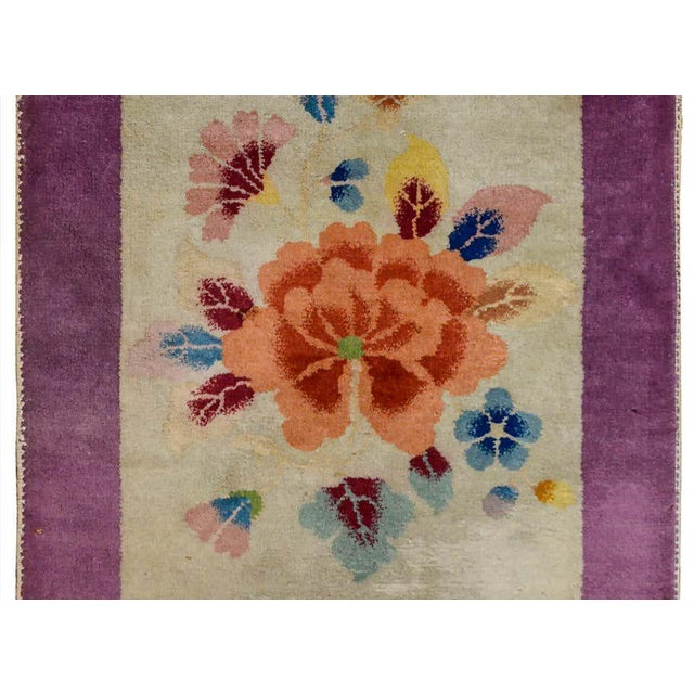 A wonderful early 20th century chinese Art Deco rug with a large coral colored peony woth more multicolored leaves and...