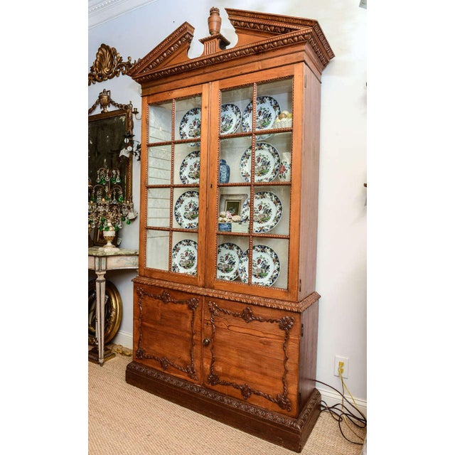 Neoclassical cabinet, of pumpkin pine, surmounted by broken pediment elaborately carved with dentil molding and egg-and-...