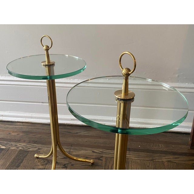 """A stunning pair of mid-1950s brass and.5"""" thick glass-top drinks tables by Italian designer Cesare Lacca. Each table..."""