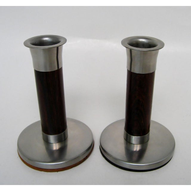 A pair of Scandinavian stainless steel and dark-stained wood candlesticks with architectural column-styling. Both have...