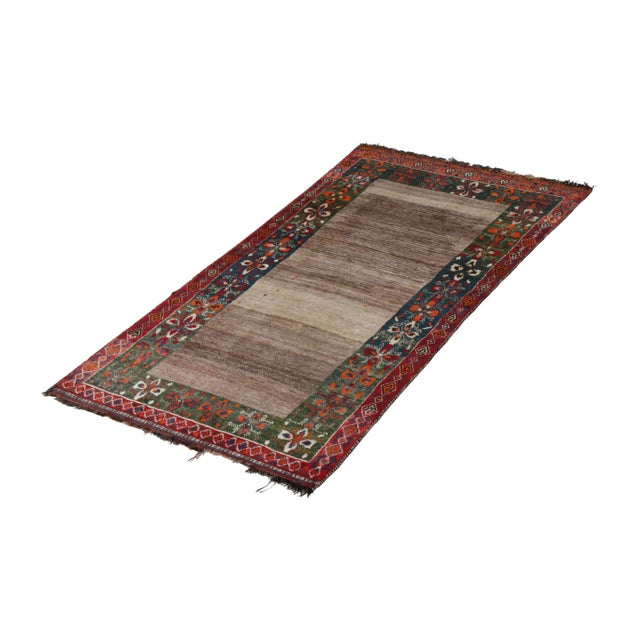 Hand-knotted in wool pile originating circa 1950-1960, this vintage Persian rug connotes a mid-century Gabbeh tribal rug...