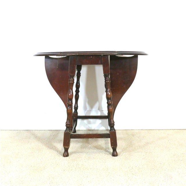Offering an elegant folding table from the Edwardian era, circa 1910. Constructed of hardwood and brass connectors....
