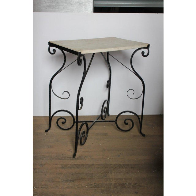 This is an antique French wrought iron and marble table.