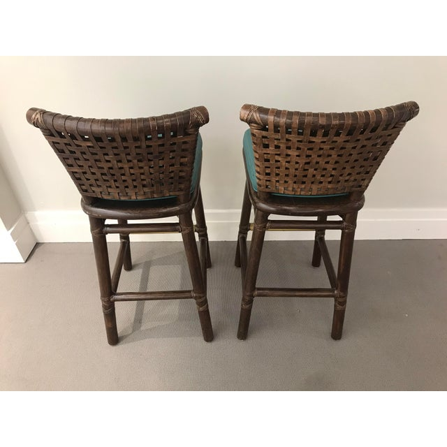 Pair of McGuire San Francisco leather banded bar stools. These bar stools were custom upholstered with teal faux leather....