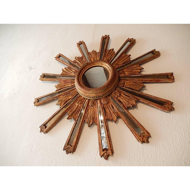 Giltwood with 13 mirrored rays. Centre mirror measures approx. 4.5 inches. One small break in one mirrored ray as shown.