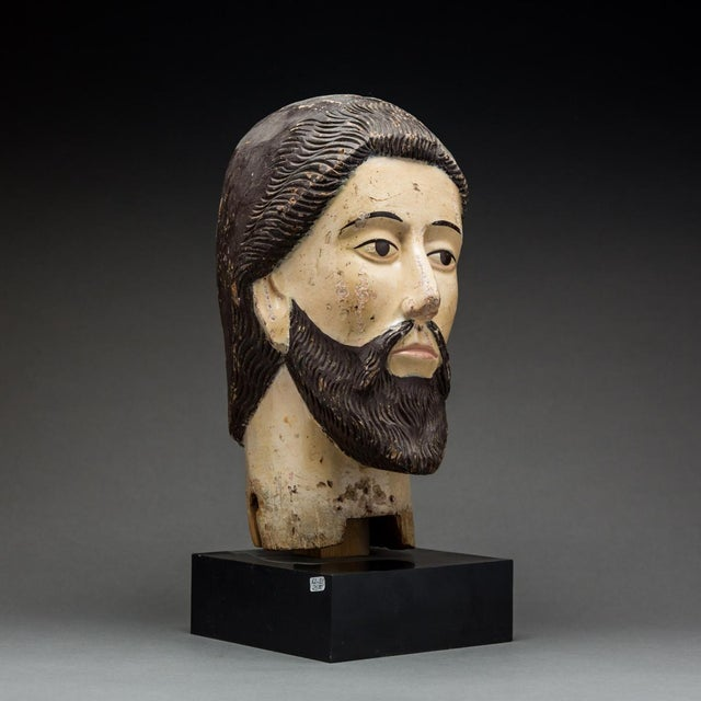 Carved out of solid wood, covered in gesso and painted in semi-naturalistic way, this head may represent either a saint or...