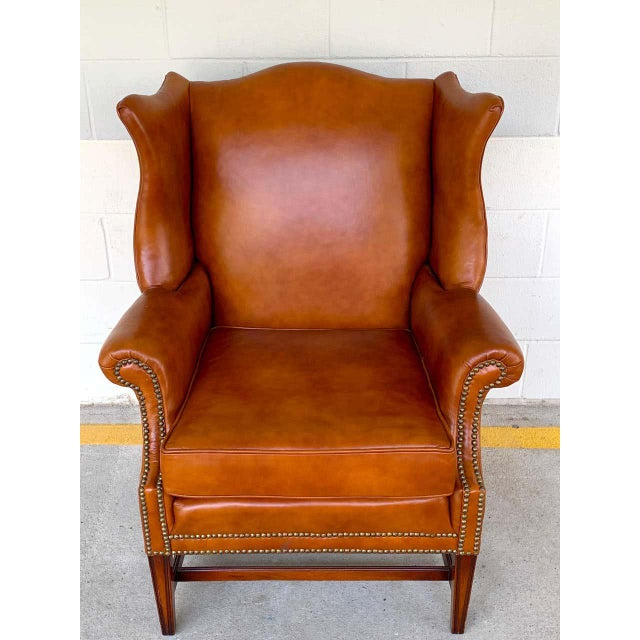 English saddle leather mahogany wingback chair, beautifully shaped lush leather wing chair with brass nailheads, raised on...