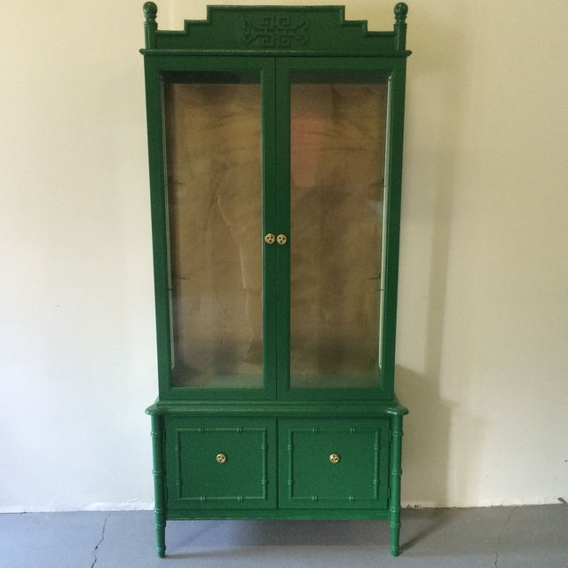 Vintage faux bamboo style hutch with gold interior back panel. Interior top has 2 glass shelves and the 2 lower cabinet...