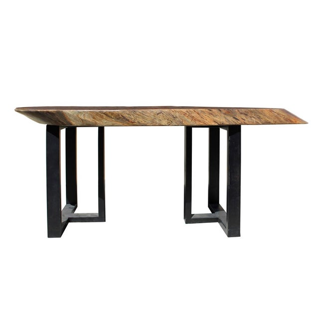 This is a polished uneven shape raw wood plank table / desk with black color metal base. The surface shows the wood tree...