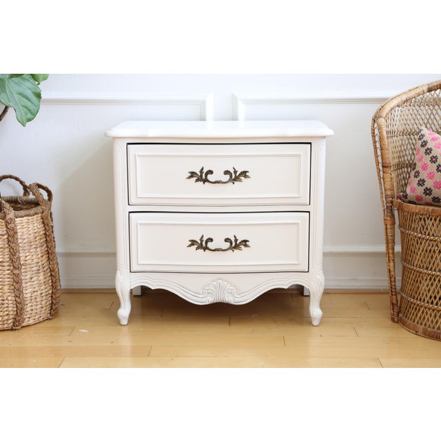 Beautiful French Provincial nightstand features solid wood with a white paint finish. This shabby chic night stand is in...