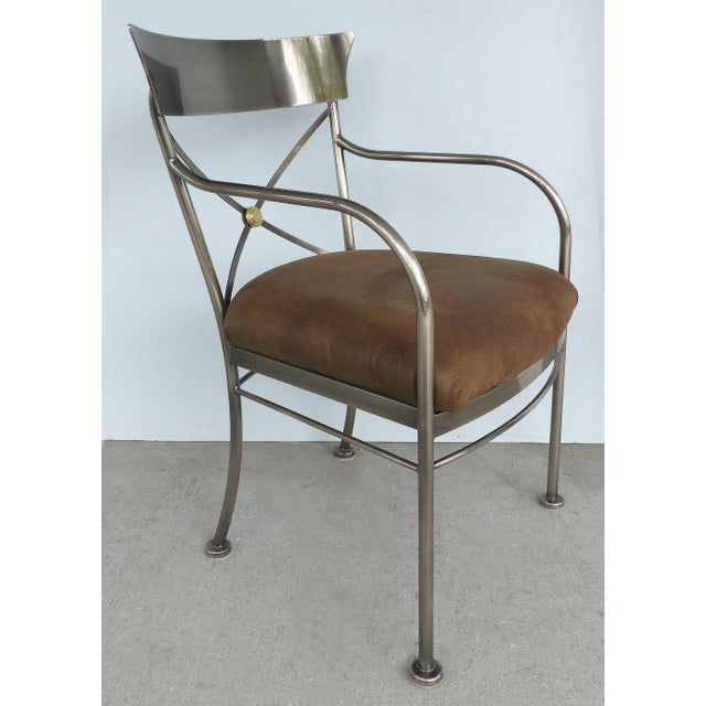 Offered for sale is a set of six Italianate steel, brass and leather dining chairs by the Design Institute of America...