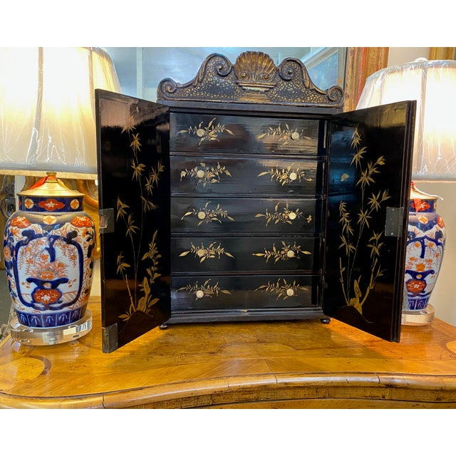 A black and gold 19th century chinoiserie table top chest with five drawers, with key.