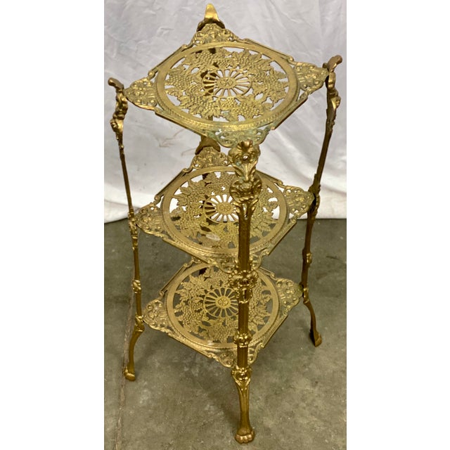 A vintage solid brass 3 tier stand, ca. 1910-1920. The stand has a grape and cherub motif on each tier with paw feet and...