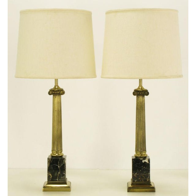 Pair of neoclassical ionic column table lamps with black Italian portoro marble block bases. Reeded brass columns with...