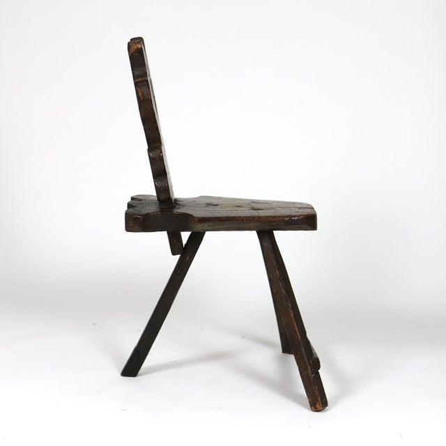 A rustic carved oak Tyrolean three-legged chair; Austria circa 1680; height: 36 in. 92.5 cm., width 23 in. 58.5 cm.,...