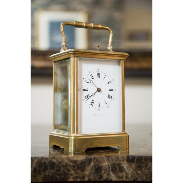 Brass case with glass on all sides and top with handle on top. Roman numeral face having dial to set fare amount for trip...
