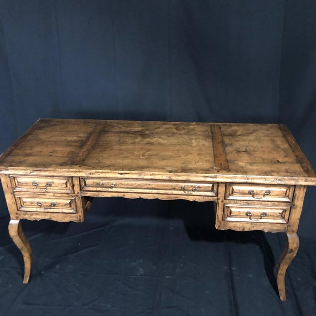 A lovely country French Provincial desk by Guy Chaddock from the Melrose Collection. The desk is made of mixed light woods...