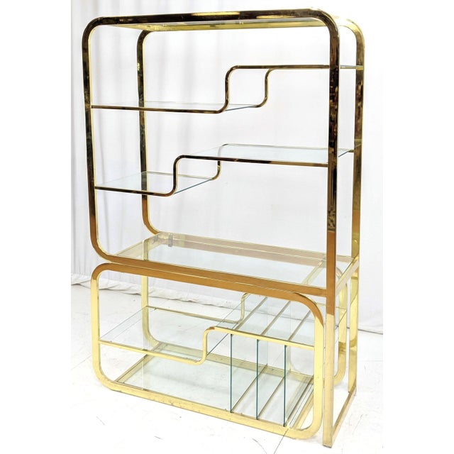 A Milo Baughman for Design Institute of America curvilinear brass and glass modular etagere. A curved brass frame supports...