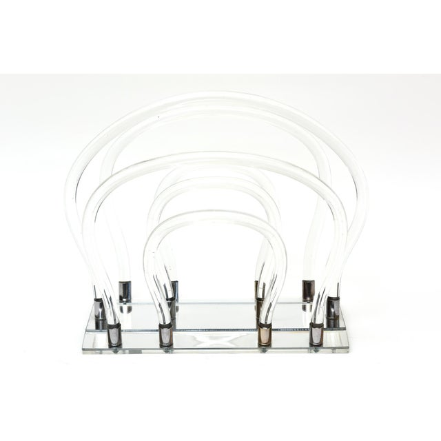 A genuine Dorothy Thorp Magazine rack in her signature tubular lucite acrylic and chromed metal fitted onto a mirrored base.