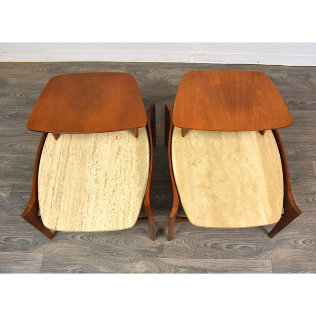 A pair of mid century modern solid walnut two tier end tables made with Italian travertine tops designed by Bertha...