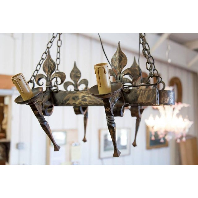 Hand-forged iron four-light Country French chandelier with wonderful patina. This oval chandelier with fleur de lis...