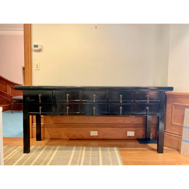 This beautiful wooden console in a black lacquer finish features lovely hanging metal pulls with an understated asian...