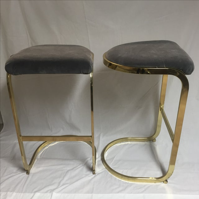 Pair of vintage brass stools in the style of Milo Baughman. Newly upholstered in a luxurious velvet gray fabric. A...