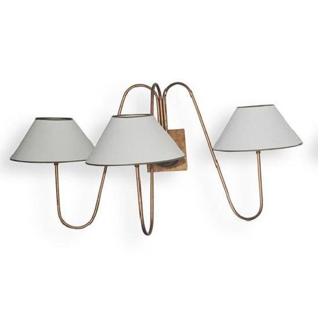 Pair of three light bouquet wall sconces, after Jean Royère, Each one of gilded iron, secured with square backplate....