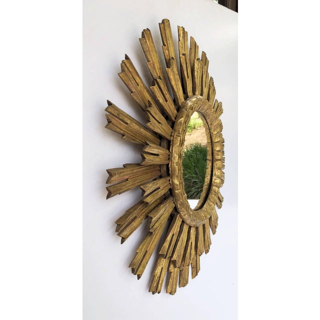 A lovely French gilt sunburst (or starburst) mirror, 25 inches diameter, with round mirrored glass centre in moulded frame.