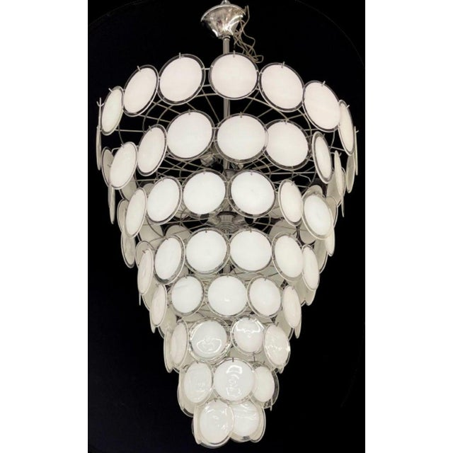 An impressive palatial pair of Mid-Century Modern circular disc white alternating color chandelier. These are large...