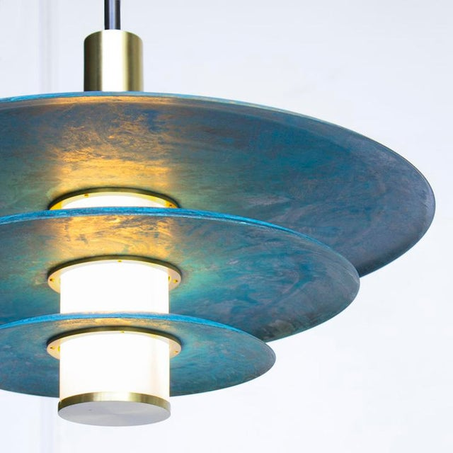 The tiered Arthur pendant embraces Trella's Prussian blue patina in grand fashion. An internally lit white glass cylinder...