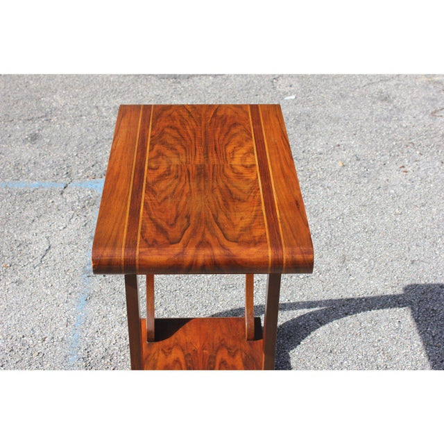 French art deco period coffee table. Made in the 1940s from exotic walnut. Wwo-top shelves supported by four legs that...