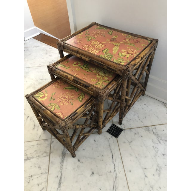 Vintage set of three bamboo nesting tables in graduating sizes. Tops are comprised of a chintz fabric with a plastic...