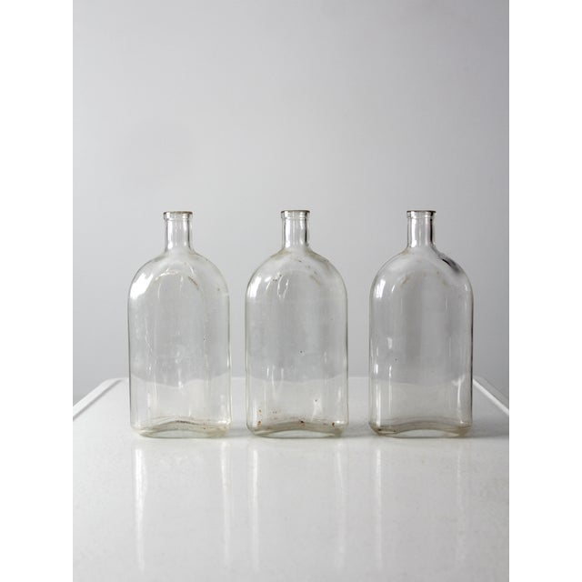 This is a collection of three Pyrex apothecary bottles. The large clear glass bottles feature a flat base, a rounded front...