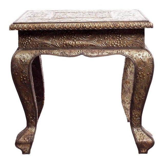 A square Indian table with flower patterns made with hammered and detailed silver. The table showcases a square top...