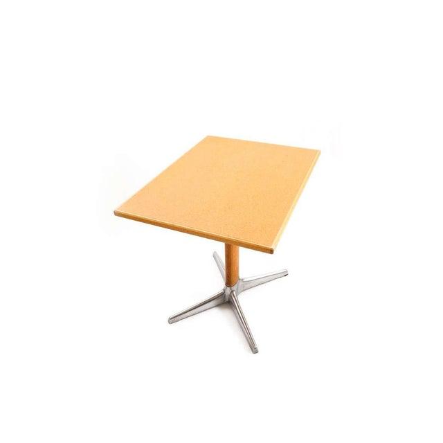 Elegant table by the Austrian architect Oswald Haerdtl featuring an aluminium cast base and oval shaped walnut stem.