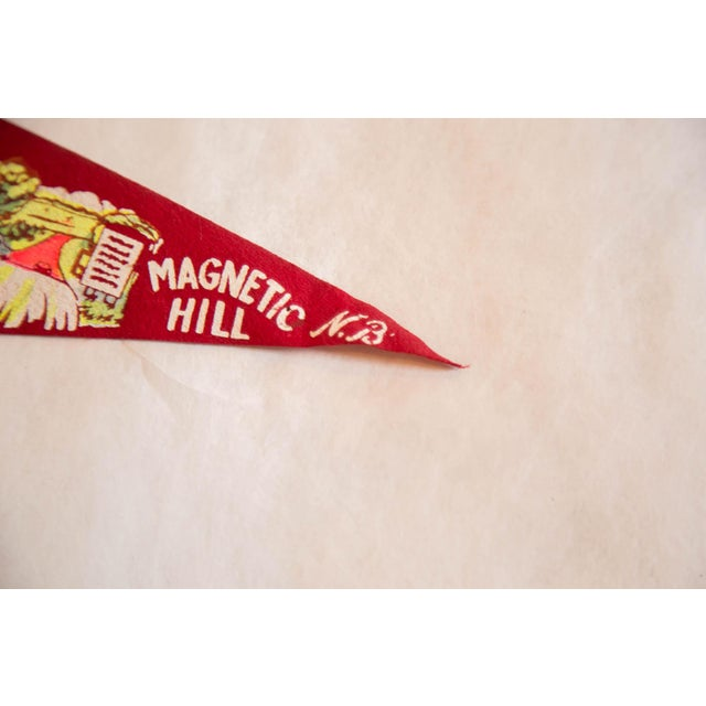 :: Vintage felt flag pennant from Magnetic Hill in New Brunswick, Canada. Features colorful imagery of a building, cars,...