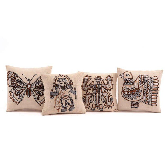 Set of four embroidered wool pillows form Peru, circa late 1960s. These examples have hand embroidered animal and figural...
