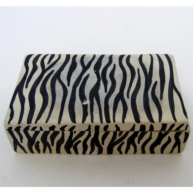 African hand-carved ivory soapstone lidded box in rectangular shape and hand-painted black zebra pattern. No maker's mark,...