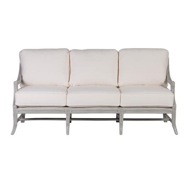 This David Francis sofa features a rattan frame with rawhide bindings and an upholstered webbed deck . This sofa was hand...