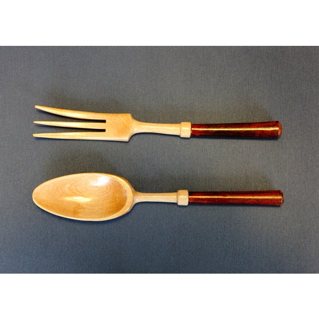 This vintage salad fork and spoon set is made of wood. The two wood tones compliment each other and give versatility for...