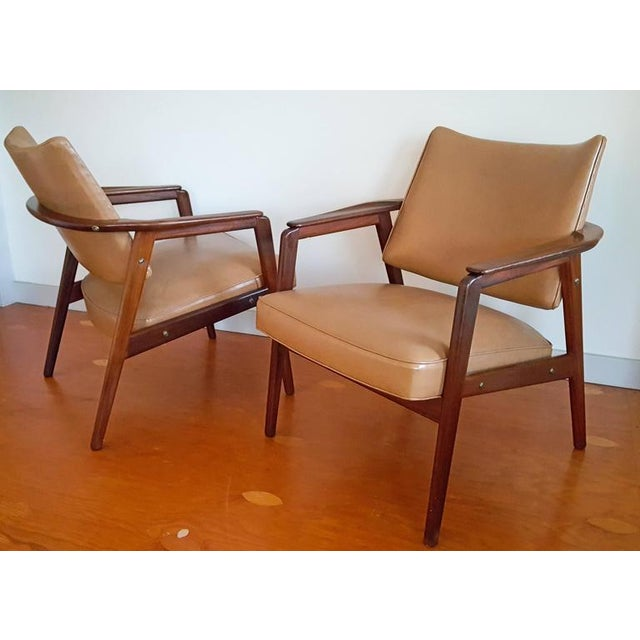 A stunning pair of Mid-Century sculptural teak lounge chairs in the style of Sigvard Bernadotte. These stunning chairs...