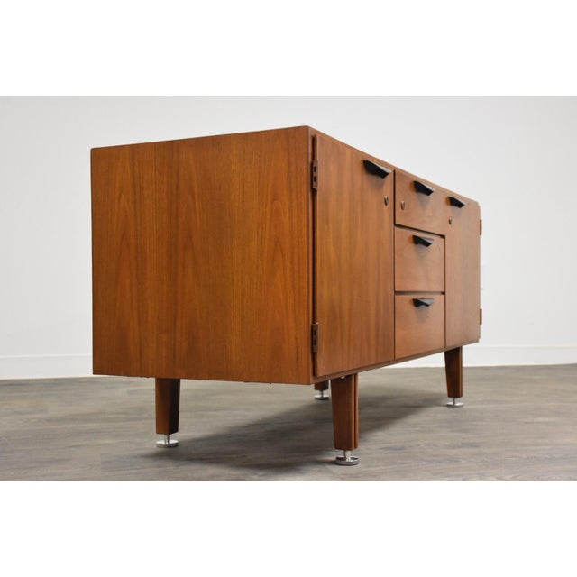 A mid century modern walnut office credenza or server with cabinet and drawer space by Jens Risom. Black metal drawer...